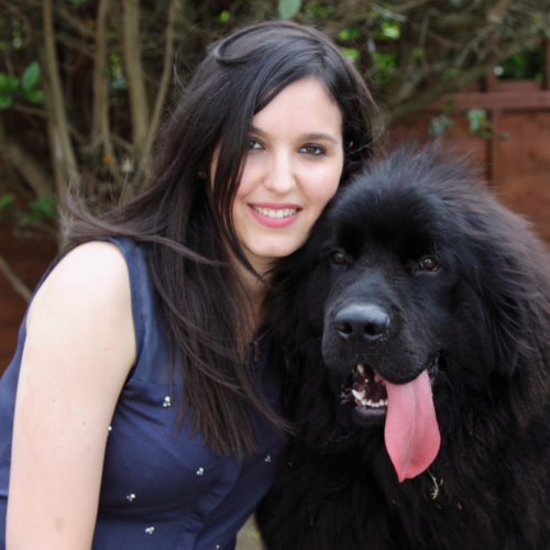 Photograph of women next to a large black dog.